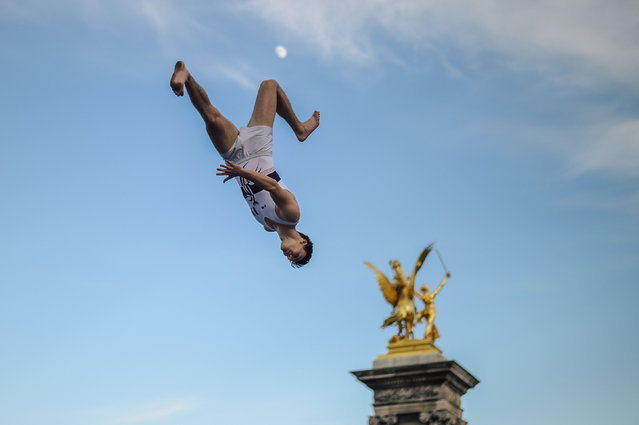 """French trampoline athlete performs in front of the public on the Pont Alexandre III in the center of Paris during the """"Olympics Day"""" organized by the city of Paris and the """"Comité National Olympique et Sportif Français"""" (CNOSF) to celebrate the upcoming of the 2024 Paris Olympics Games, in Paris on June 23, 2018. (Photo by Lucas Barioulet/AFP Photo)"""