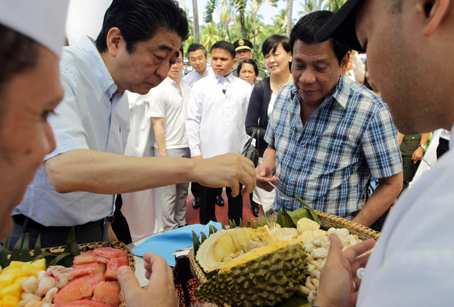 President Rodrigo Duterte and Japan's Prime Minister Shinzo Abe (L) try durian fruit after attending various events at the Waterfront Hotel in Davao City, southern Philippines January 13, 2017. (Photo by Reuters/Malacanang Photo)