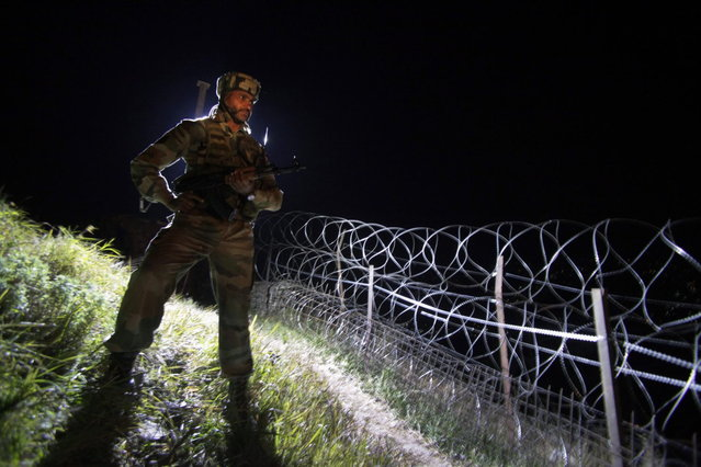 In this December 22, 2013 photo, an Indian army soldier stands guard along barbed wire near the Line of Control (LOC), that divides Kashmir between India and Pakistan, at Krishna Ghati (KG Sector) in Poonch, 290 kilometers (180 miles) from Jammu, India. (Photo by Channi Anand/AP Photo)
