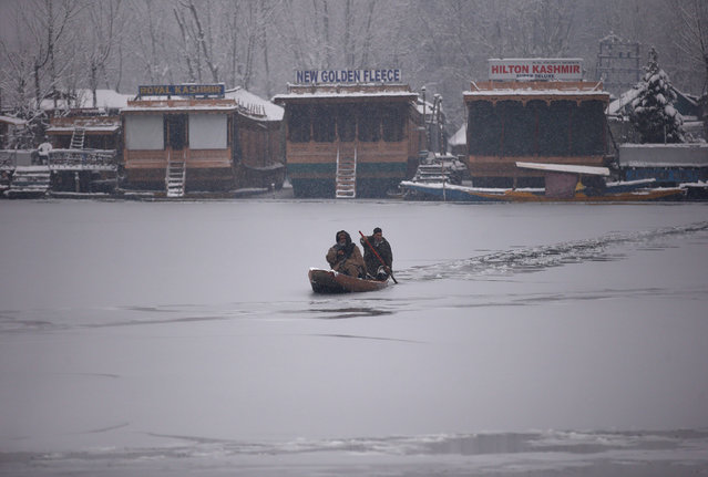 A man rows his small boat on the partially frozen Dal Lake during a snowfall in Srinagar January 16, 2017. (Photo by Danish Ismail/Reuters)