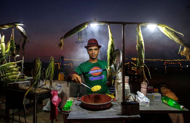 A Palestinian man sells corn at Gaza Beach during sunset on August 8, 2021. (Photo by Sameh Rahmi/NurPhoto/Rex Features/Shutterstock)