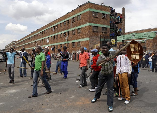 A crowd of anti-immigrant protesters demonstrate outside the Jeppe hostel in Johannesburg, South Africa, Friday, April 17, 2015, where some foreigners have sought refuge. (Photo by Themba Hadebe/AP Photo)