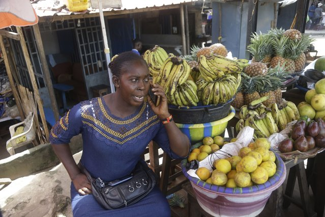 A woman a takes a phone call as she sells fruit on a street in Conakry, Guinea Thursday, September 9, 2021. (Photo by Sunday Alamba/AP Photo)