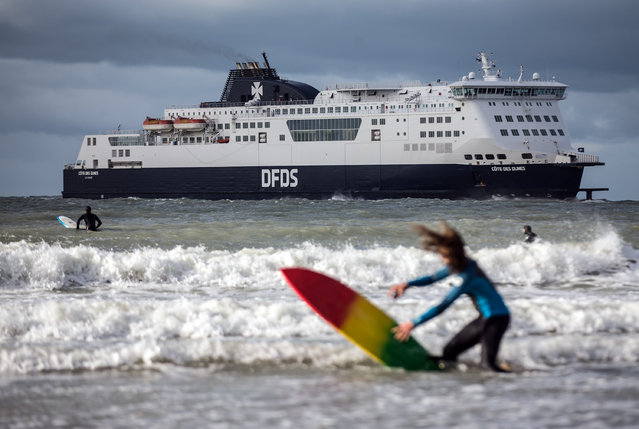 A surfer drops her board as a cross-channel ferry approaches port on February 28, 2016 in Calais, France. (Photo by Carl Court/Getty Images)