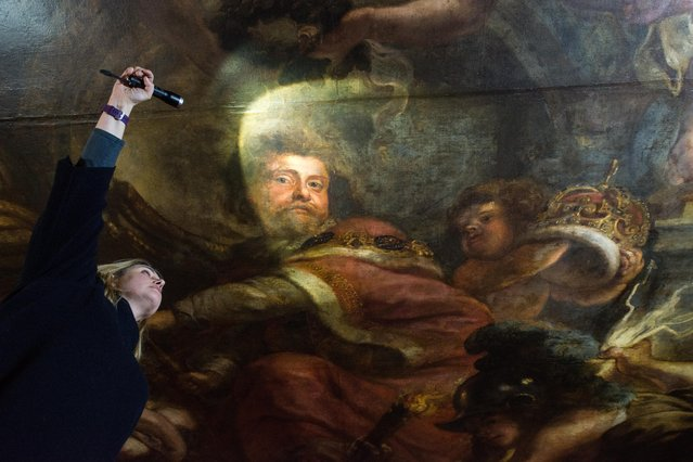"""Conservationist Sarah Pinchin, 41, inspects her teams work on Rubens ceiling painting """"Wise rule of James 1st"""" and shines a light on an image of James 1st during restoration work at Banqueting House on March 1, 2016 in London, England. The Banqueting House is the only remaining part of the Palace of Whitehall, once the largest Palace in Europe but destroyed by fire in 1698. Visitors can see the magnificent ceiling painted by Sir Peter Paul Rubens. It is currently being renovated and will re-open to the public on April 1st. (Photo by Chris Ratcliffe/Getty Images)"""