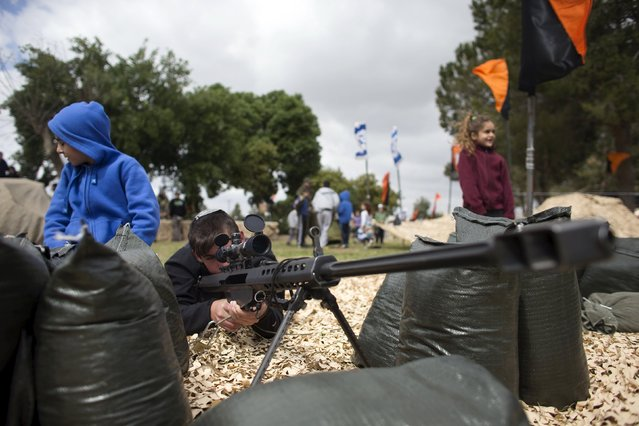 An Israeli youth looks through the sight of a weapon during a display of Israeli Defense Forces (IDF) equipment and abilities at the West Bank settlement of Kiryat Arba, April 23, 2015, during celebrations for Israel's Independence Day, marking the 67th anniversary of the creation of the state. (Photo by Ronen Zvulun/Reuters)