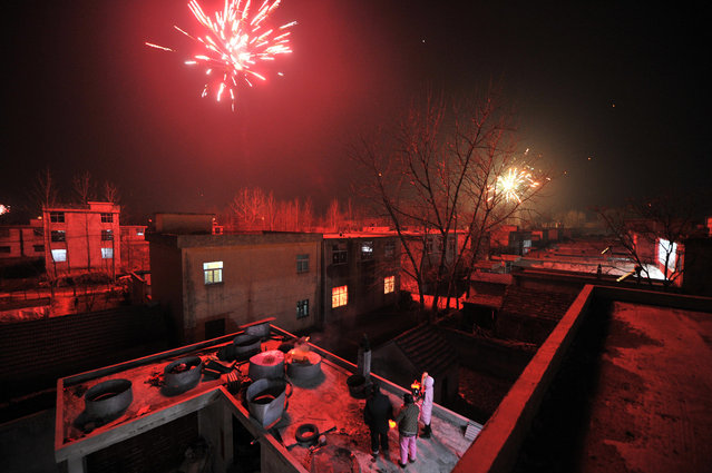 People watch firework explode from a rooftop on the eve of the Chinese Lunar New Year, or the Spring Festival, in Mengcheng, Anhui province, China January 27, 2017. (Photo by Reuters/Stringer)
