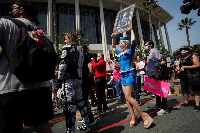 Nefertara, a supporter of pop star Britney Spears, wears an outfit inspired by the singer as she holds a picture of Britney that she painted, during a gathering on the day of a conservatorship case hearing at Stanley Mosk Courthouse in Los Angeles, California, U.S., September 29, 2021. (Photo by Mario Anzuoni/Reuters)
