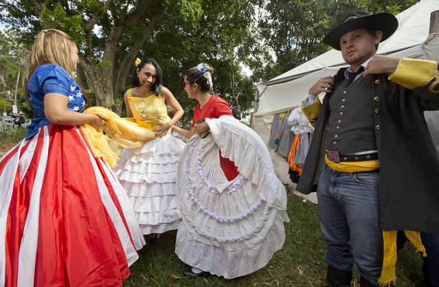 Descendants of American Southerners Wearing Confederate-era dresses and uniform prepare to attend a party to celebrate the 150th anniversary of the end of the American Civil War in Santa Barbara d'Oeste, Brazil, Sunday, April 26, 2015. (Photo by Andre Penner/AP Photo)