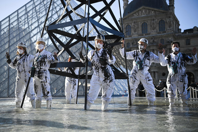 """Greenpeace activists wearing the uniform of petroleum workers stand beside a smoking """"oil well tower"""" during an action in front of The Louvre Museum Pyramid in Paris on October 6, 2021 as they protest against French energy company Total and continued world fossil fuel production and consumption. (Photo by Anne-Christine Poujoulat/AFP Photo)"""
