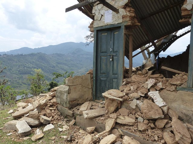 In this Monday, April 27, 2015, photo provided by the International Nepal Fellowship, a lone doorway is seen in the rubble of a collapsed home 25 kilometers (15.5 miles) from the epicenter of Saturday's massive earthquake in Pokhridada, Gorkha district, Nepal. (Photo by Thomas Meier/International Nepal Fellowship via AP Photo)