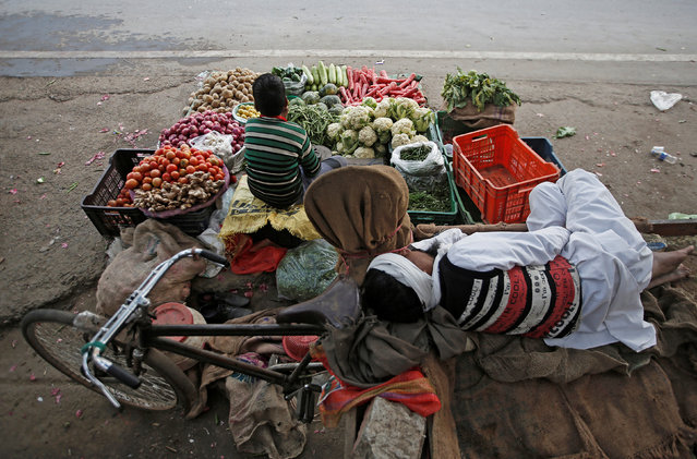 A vendor sleeps as his son waits for customers at their roadside vegetable shop in New Delhi, February 12, 2019. (Photo by Adnan Abidi/Reuters)
