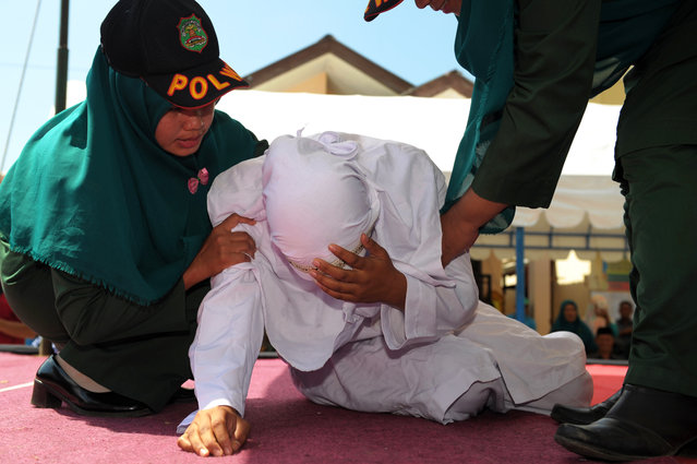 An Indonesian woman known as Linda (C) is helped by two Sharia officials after being caned for spending time in close proximity with a man who is not her husband, which is against Sharia law, in Banda Aceh on February 2, 2017. Aceh is the only province in the world's most populous Muslim-majority country that imposes sharia law. People can face floggings for a range of offences – from gambling, to drinking alcohol, to gay s*x. (Photo by Chaideer Mahyuddin/AFP Photo)