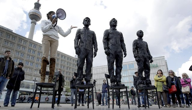"A woman delivers a speech as she stands on a chair of the public art project ""Anything to Say?"" at the Alexander Square in Berlin, Germany, Friday, May 1, 2015. The sculpture of the Italian artist Davide Dormino shows the whistleblowers Chelsea Manning, Julian Assange and Edward Snowden, from right, to honour their courage. (Photo by Michael Sohn/AP Photo)"