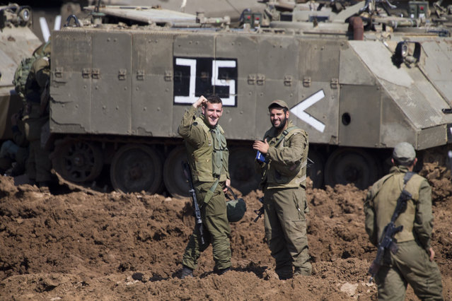 Israeli soldiers react as they work on their vehicles at a gathering area near the Israel-Gaza border, in southern Israel, Tuesday, March 26, 2019. Israeli Prime Minister Benjamin Netanyahu returned home from Washington on Tuesday, heading straight into military consultations after a night of heavy fire as Israeli aircraft bombed Gaza targets and the strip's militants fired rockets into Israel. (Photo by Ariel Schalit/AP Photo)