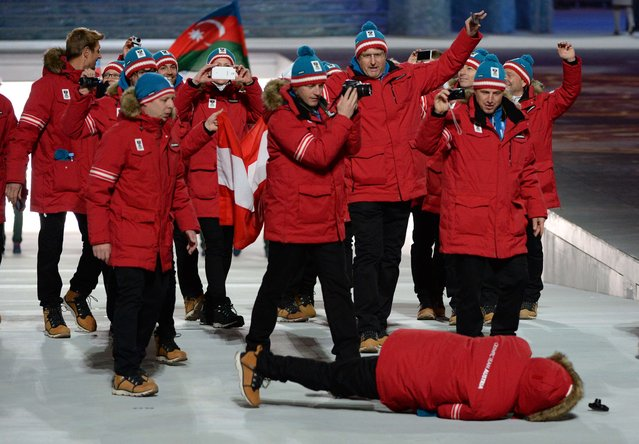 A member of Austria's delegation lies on the ground after falling during the Opening Ceremony of the Sochi Winter Olympics at the Fisht Olympic Stadium on February 7, 2014 in Sochi. (Photo by Andrej Isakovic/AFP Photo)