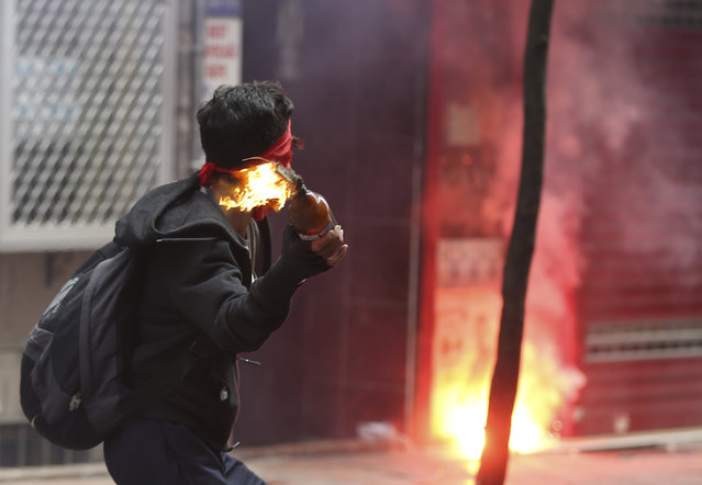 A demonstrator throw a firebomb during clashes with Turkish riot police officers in Istanbul, Turkey, Friday, May 1, 2015. The government assigned 30,000 police officers backed by helicopters as workers and demonstrators determined to defy a government ban, tried to march to iconic Taksim Square, where 35 people were killed during May Day celebration in 1977. (Photo by Emrah Gurel/AP Photo)