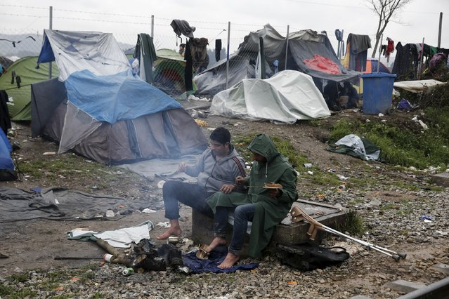A handicapped migrant (L) and his comrade warm themselves next to a bonfire at a makeshift camp at the Greek-Macedonian border, near the village of Idomeni, Greece March 15, 2016. (Photo by Alkis Konstantinidis/Reuters)