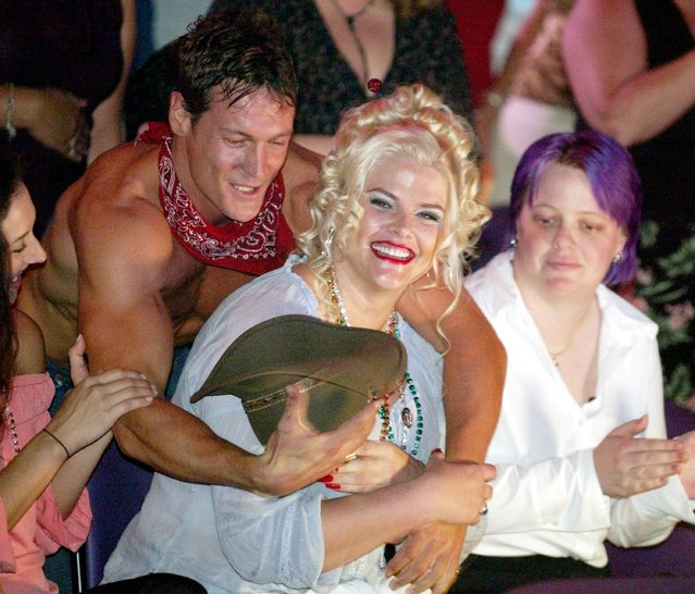 Chippendales dancer Nathan Minor jokes with Anna Nicole Smith during a Chippendales show at the Rio Hotel & Casino July 18, 2002 in Las Vegas, Nevada. Smith's friend Kimmie Walther is at right. (Photo by Ethan Miller/Getty Images)