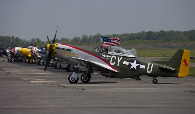 The pilot of a P51 Mustang waves the American flag after a practice flight with dozens of World War II era aircraft at Culpeper Regional Airport in Brandy Station, Virginia, May 7, 2015. (Photo by Andrew Caballero-Reynolds/AFP Photo)