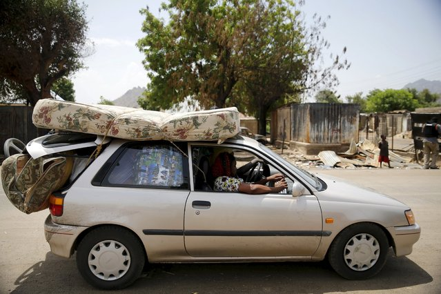 People travel in a car with their belongings as they return after the Nigerian military recaptures the town of Michika from Boko Haram, Adamawa state May 10, 2015. (Photo by Akintunde Akinleye/Reuters)