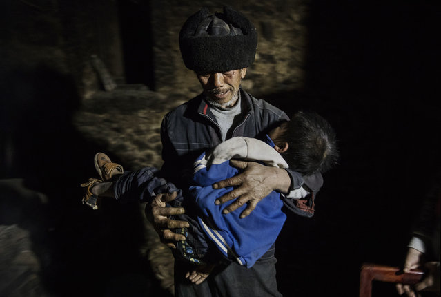 """Grandfather Luo Yingtao, 64, carries his grandson """"left behind"""" child Luo Lie, 5, to bed at the family house on December 17, 2016 in Anshun, China. (Photo by Kevin Frayer/Getty Images)"""