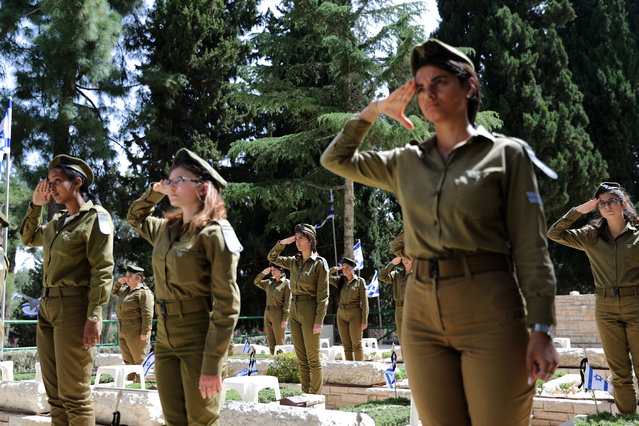 "Israeli female soldiers salute after decorating graves of fallen soldiers with small Israeli national flags, at the Mount Herzl (Mount of Remembrance) military cemetery in Jerusalem, Israel, 06 May 2019. Israel is preparing to mark its ""Day of Remembrance for the Fallen Soldiers of Israel and Victims of Terrorism"", which will begin at sunset on 07 May 2019. (Photo by Abir Sultan/EPA/EFE)"