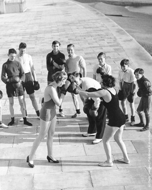 1935:  Two female members of a keep fit group learn boxing techniques as part of self defence lessons