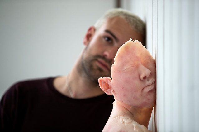 Fine Art student Hugo Harris alongside his model sculpture titled Press at the media preview of the Edinburgh College of Art degree show in Edinburgh, Scotland on May 30, 2019. (Photo by Jane Barlow/PA Images via Getty Images)
