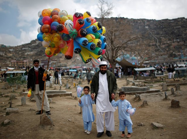 An Afghan man and his sons look on as they walk past a man who sells balloons  near a shrine to celebrate the Afghan New Year (Newroz) in Kabul March 21, 2014. (Photo by Ahmad Masood/Reuters)