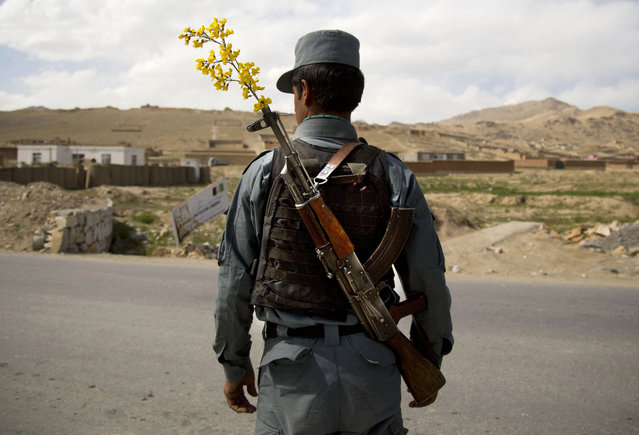 In this May 15, 2013 file photo, an Afghan National Police officer mans a checkpoint in the outskirts of Maidan Shahr, Wardak province, Afghanistan. (Photo by Anja Niedringhaus/AP Photo)