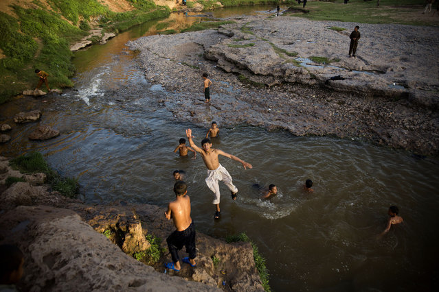 Pakistani children play in a stream polluted by sewerage from nearby localities, in a suburb of Islamabad, Pakistan, Tuesday, April 21, 2015. (Photo by B. K. Bangash/AP Photo)