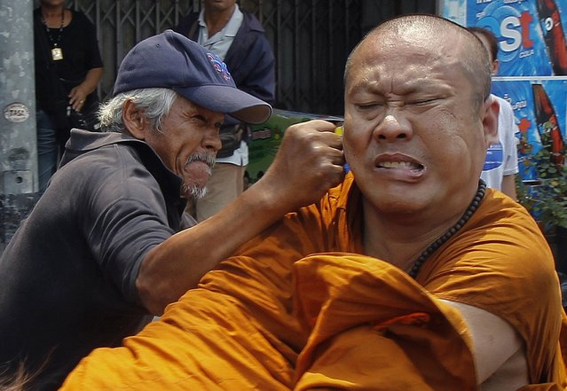 "A member of the pro-government ""red shirt"" movement attacks a Buddhist monk outside the National Anti-Corruption Commission office in Nonthaburi province, on the outskirts of Bangkok March 24, 2014. Members of the movement attacked the monk after he shouted complaints to the group blocking a road near the National Anti-Corruption Commission. (Photo by Chaiwat Subprasom/Reuters)"