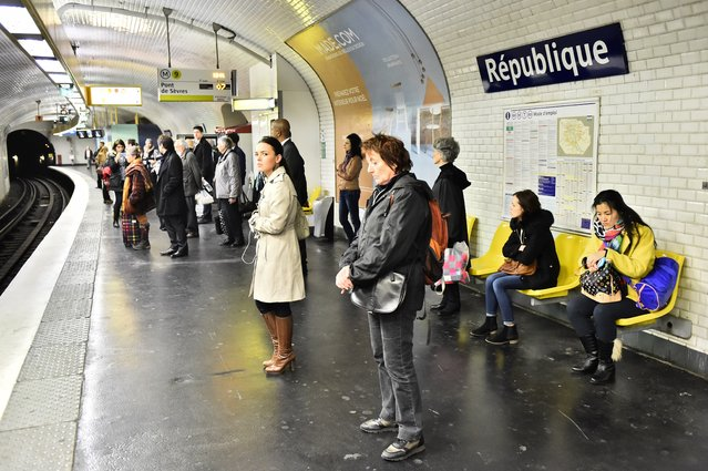 People observe a minute of silence, on November 16, 2015 at Republique subway station in Paris, to pay tribute to victims of the attacks claimed by Islamic State which killed at least 129 people and left more than 350 injured on November 13. France and other countries in Europe held a minute's silence in memory of the victims of the worst ever terror attacks on French soil. (Photo by Loic Venance/AFP Photo)
