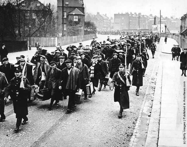 1914: New recruits march alongside armed officers following the outbreak of the First World War