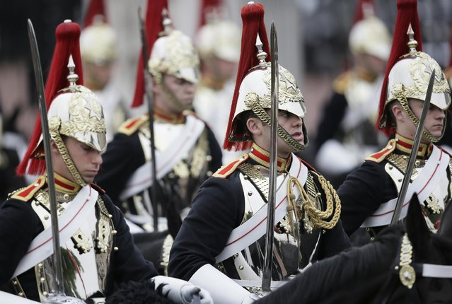 """Soldiers of the Household Cavalry wait for the arrival of the carriages during the Trooping The Colour parade at Buckingham Palace, in London, Saturday, June 13, 2015. Hundreds of soldiers in ceremonial dress have marched in London in the annual Trooping the Color parade to mark the official birthday of Queen Elizabeth II. The Trooping the Color tradition originates from preparations for battle, when flags were carried or """"trooped"""" down the rank for soldiers to see. (AP Photo/Tim Ireland)"""