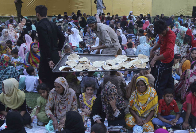 Pakistani volunteers distribute food among people at a roadside to break their fast during the Muslim fasting month of Ramadan, in Lahore, Pakistan, Thursday, May 9, 2019. Muslims around the world are observing Ramadan, the holiest month in Islamic calendar. (Photo by K.M. Chaudary/AP Photo)