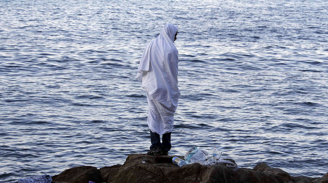 A migrant wrapped in a white a blanket stands on the rocks of the seawall at the Saint Ludovic border crossing on the Mediterranean Sea between Vintimille, Italy and Menton, France, June 17, 2015. Police on Tuesday began hauling away mostly African migrants from makeshift camps on the Italy-France border as European Union ministers met in Luxembourg to hash out plans to deal with the immigration crisis.    REUTERS/Eric Gaillard