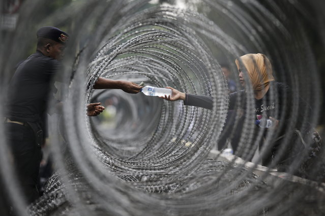 An Indonesian police officer buys a bottle of water through razor wire as he stands guard outside the Constitutional Court in Jakarta, Indonesia, 14 June 2019. Indonesia's authorities tightened security as trial hearings started in court to challenge the results of the presidential election. (Photo by Mast Irham/EPA/EFE)