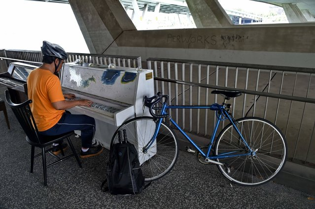 A man plays a public piano under the Marina bridge in Singapore on April 26, 2016. Six pianos are scattered across the Marina Bay by the Play It Forward Singapore movement so that everyday Singaporeans can have access to them. (Photo by Roslan Rahman/AFP Photo)