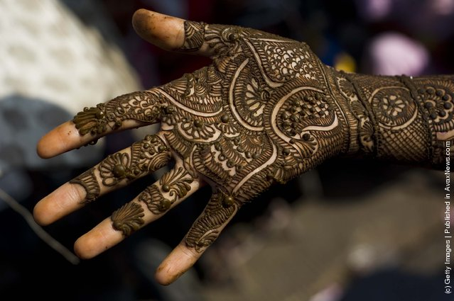 "Application of henna or ""Mehndi""  to a girls hand in a market in Jaipur, India"