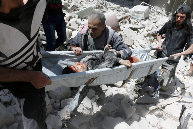 A man follows rescuers carrying the body of a boy on a stretcher following a reported air strike on the rebel-held neighbourhood of al-Kalasa in the northern Syrian city of Aleppo, on April 28, 2016. (Photo by Ameer Alhalbi/AFP Photo)