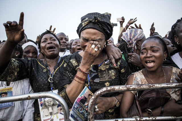 Supporters of late former DR Congo Prime Minister and opposition leader Etienne Tshisekedi, react as his remains come past ahead of his burial on June 01, 2019 in Kinshasa. The remains of Etienne Tshisekedi, the Democratic Republic of Congo's revered opposition leader, arrived in Kinshasa on May 30, in an emotion-laden moment for the country after his son Felix became president this year. An opponent of authoritarianism in DRC, Tshisekedi died in Belgium in February 2017 at the age of 84, and he was unable to witness his son's victory in bitterly contested election at the end of last year. (Photo by John Wessels/AFP Photo)