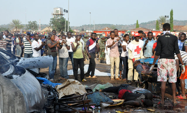 People gather at the site of a blast at the Nyanya Motor Park, about 10 miles from the center of Abuja, Nigeria. An explosion occurred at a busy commuter bus station on the outskirts of Abuja as hundreds of people were traveling to work. (Photo by Afolabi Sotunde/Reuters)