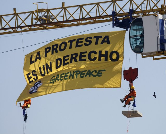 Greenpeace activists hang with a banner from a crane above the Spanish parliament in Madrid, Spain, June 30, 2015. (Photo by Andrea Comas/Reuters)