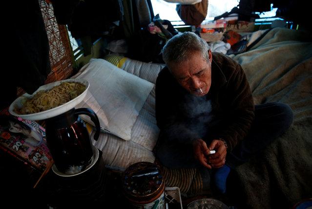 Homeless Makoto Shinbo smokes a cigarette at his makeshift house in Miyashita park in Tokyo, Japan, February 17, 2017. (Photo by Kim Kyung-Hoon/Reuters)