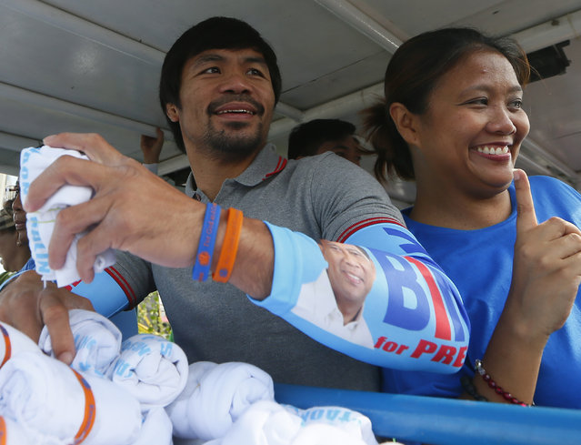 Congressman Manny Pacquiao, left, who is running for senator in Monday's national elections, poses with Sen. Nancy Binay, the daughter of presidential candidate Jejomar Binay during their campaign rally, in Navotas north of Manila, Philippines, Friday, May 6, 2016. (Photo by Bullit Marquez/AP Photo)
