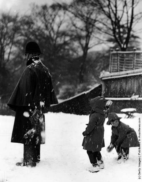 1960: Two children throwing snowballs at a policeman