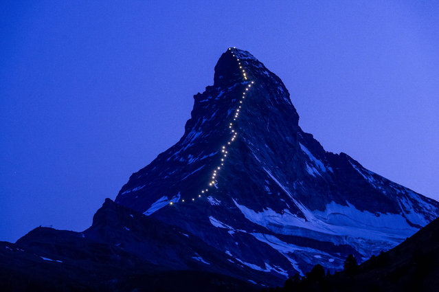 In this picture made available Thursday, July 9, 2015, lamps illuminate the path of the first ascent on the Matterhorn mountain, in Zermatt, Switzerland, late Wednesday, July 8, 2015. On the 14th of July, Zermatt celebrates 150 years since the first ascent of the Matterhorn mountain 4,478 metres above sea level. (Photo by Jean-Christophe Bott/Keystone via AP Photo)