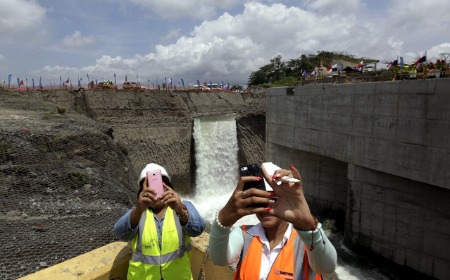Women take selfies in front of a waterfall during the flooding of the Panama Canal Expansion project on outskirts of Colon City June 11, 2015. (Photo by Carlos Jasso/Reuters)